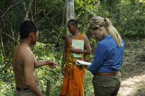 Visattha In (left) and Kelsey Pischke (right) learn about forest plants and their medicinal uses from Venerable Bun Saluth in Sorng Rokavorn (The Monks Forest).