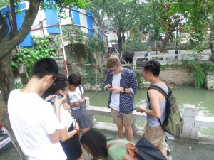 John-Michael swapping WeChat information with new friends in a town in Wujiang.