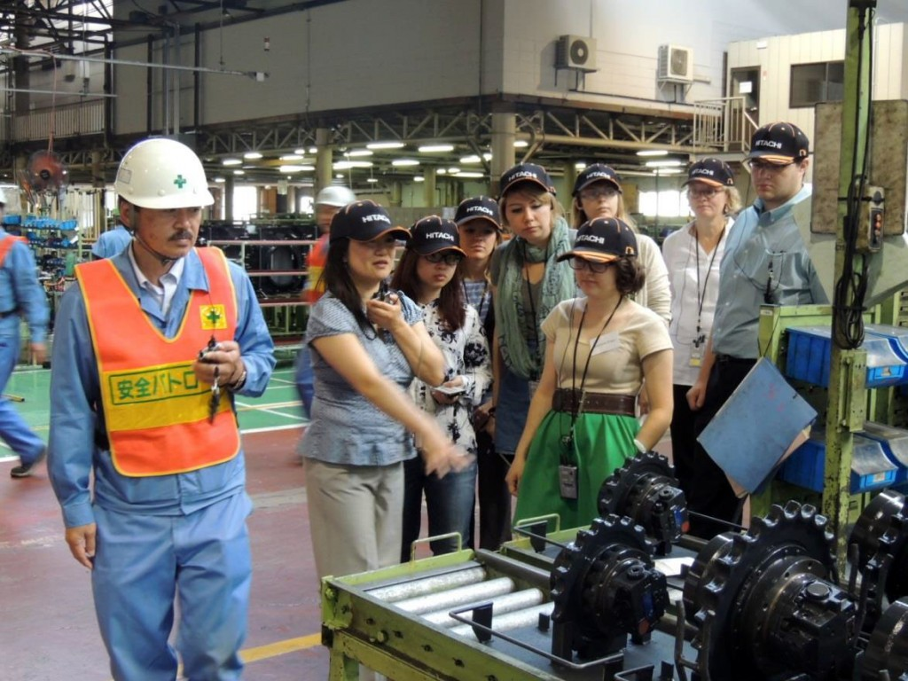 Student researchers walking through Hitachi Kenki Tierra factory while observing the workers and the process of excavator manufacturing.