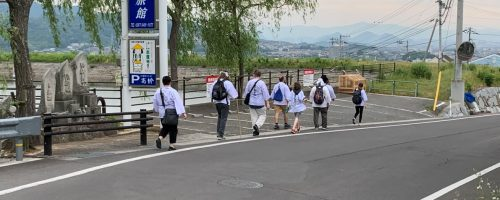 This photo illustrates the suburban area where Shikoku pilgrims travel between the first temples in the pilgrimage. The group is passing a sign for an inn that caters to pilgrims.